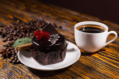 Delicious dark chocolate cupcake by coffee mug. Delicious dark chocolate cupcake decorated with red berries by white coffee mug and pile of beans on wooden table Royalty Free Stock Photo