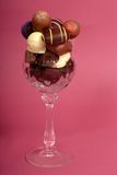 Delicious dark and semi-sweet chocolates in a cut crystal wine g Stock Photography
