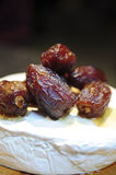 Delicious dates on camembert cheese. Delicious gourmet dessert with giant dates on camembert cheese, with honey poured over the dates Stock Images