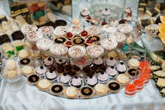 Delicious decorated candy bar, sweets on tables for wedding reception Stock Image