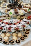 Delicious decorated candy bar, sweets on tables for wedding reception Stock Photo