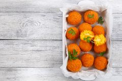 Saffron rice balls stuffed with cheese. Delicious deep fried sicilian arancini - saffron rice balls stuffed with cheese in baking dish on old wooden table Stock Images