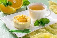 Delicate orange dessert and tea in cup Royalty Free Stock Photos