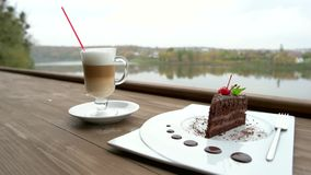Delicious dessert with cappucino on outdoor terrace. Brownie cake and glass of latte at outdoor cafe table. Best coffee break in favorite restaurant stock footage
