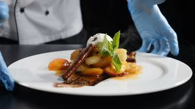 Delicious dessert in chef hands. White plate with ice-cream and fried fruits in caramel put on table. Restaurant food. Cerving. Food video in slow motion stock video footage