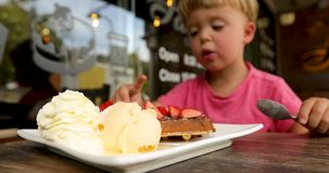 Delicious dessert closeup background eating child. Delicious dessert ice cream cake strawberries. Boy eats strawberries with pleasure spoon stock footage