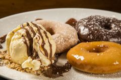 Delicious dessert donuts and ice cream on a white plate with decoration on a wooden table Royalty Free Stock Image