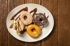 Delicious dessert donuts with ice cream on a white plate with decoration on a wooden table. Royalty Free Stock Image