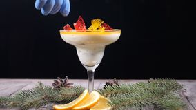 Delicious dessert in glass bowl on wooden board decorated with fir-tree branches and slices of lemon. Isolated on black stock video