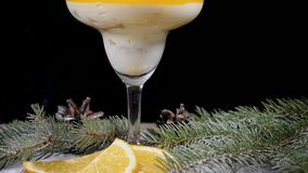 Delicious dessert in glass bowl on wooden board decorated with fir-tree branches and slices of lemon. Isolated on black. Background. Pouring sugar powder on stock footage