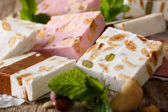 Delicious dessert: honey nougat with nuts and mint macro. horizo Royalty Free Stock Image