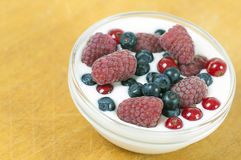 Delicious dessert made of yoghurt and ripe berries. (raspberry, red currant and blueberry royalty free stock photo