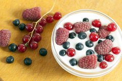 Delicious dessert made of yoghurt and ripe berries. (raspberry, red currant and blueberry royalty free stock images