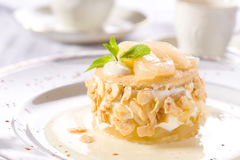 Delicious dessert with pears. Cream, nuts and fresh peppermint Stock Photography