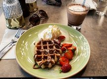 Delicious dessert with waffles, strawberries, cream and hot chocolate with sunglasses summer royalty free stock photo