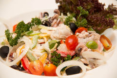 Delicious diet salad with green lettuce, red onion, slices and seafood Stock Photography