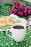 Black coffee in a white sophisticated cup, delicious dietary cheesecakes from home-made farmer cheese for breakfast, a bouquet of. Delicious Dietary Cheesecakes stock images