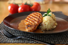 Delicious Dinner. Pork With Pepper Sauce and Cous-Cous On a Plate Royalty Free Stock Photography