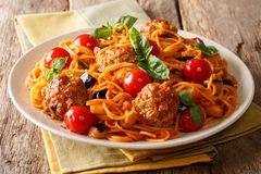 Delicious dinner: meat balls with pasta spaghetti, eggplant and. Tomatoes close-up on a plate on a table. horizontal stock photos