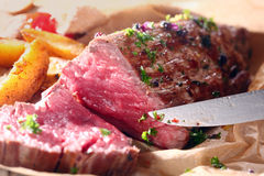 Delicious dinner of rare roast beef and potatoes. Delicious dinner of savory rare roast beef cooked with fresh herbs and potato wedges being carved for serving Royalty Free Stock Image