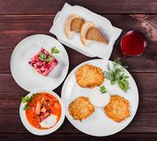 Delicious dinner table with potato pancakes, traditional beetroot soup - borscht with beef, beet salad Vinaigrette. Delicious dinner table with potato pancakes stock photography