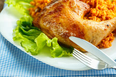 Delicious dish of chicken thigh with rice and salad leaves Stock Photo