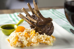 A delicious dish of Rack of Lamb with rice and apricot on a square plate. stock photos