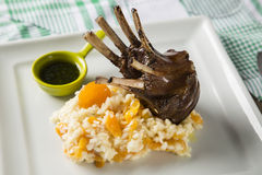 A delicious dish of Rack of Lamb with rice and apricot on a square plate. royalty free stock images