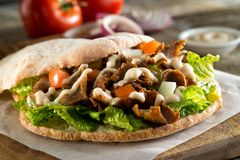 Doner Pita Sandwich. A delicious doner meat sandwich on pita bread with lettuce, tomato, onion and sauce royalty free stock images