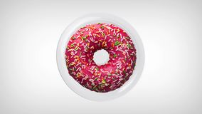 Delicious donut with colorful sprinkles, rotating on a white plate. Donut close-up. Top view.  stock footage