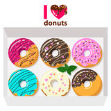 Delicious donuts in box on white background with letters: i love donuts. Royalty Free Stock Image