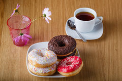 Delicious donuts on wood table with cup of tea Stock Photos