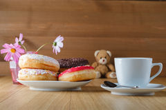 Delicious donuts on wood table with cup of tea and toy Stock Photos