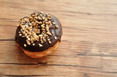 A delicious doughnut covered in peanut sprinklers. On a wooden table Royalty Free Stock Photos