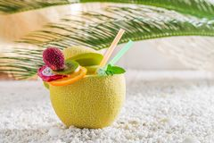 Delicious drinks in fresh fruits. On white pebbles Stock Photography