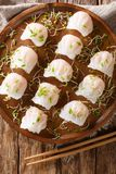 Delicious dumplings dim sum with shrimp served with sprouts close-up on a plate. Vertical top view. Delicious dumplings dim sum with shrimp served with sprouts royalty free stock images