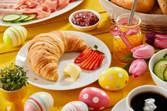 Delicious Easter breakfast on a decorated table. With colorful eggs and a freshly baked croissant and strawberry served with jam, cold meats, cheese and coffee Stock Image