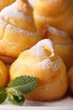 Delicious eclairs sprinkled with powdered sugar macro. Vertical Royalty Free Stock Images