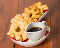 Delicious ecuadorian pristinos piled up in bowl, traditional andean pastry, cup of coffee siting on table Royalty Free Stock Photography