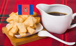 Delicious ecuadorian pristinos piled up in bowl, traditional andean pastry, cup of coffee siting on table, Quito flag Stock Image