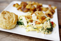 Delicious egg scramble. With marinated artichoke hearts, cheese, spinach, and red peppers served with potatoes and biscuit Stock Images
