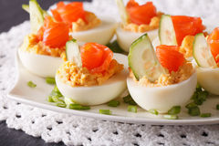Delicious eggs stuffed with salmon, cheese and cucumber closeup Royalty Free Stock Images