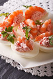 Delicious eggs stuffed with seafood close up on the table. verti Stock Photos