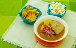 Delicious encebollado fish stew from Ecuador traditional food national dish closeup, with pocorn and some chifles of. Plantains Stock Image