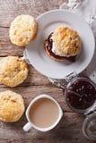 Delicious English scones with jam and tea closeup. vertical top Stock Photos