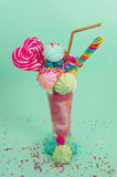 Delicious extreme milkshake of strawberry with dragees and a blackberry candy over a milk foam with a plastic straw and. A heart candy on top, with some stock image