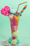Delicious extreme milkshake of strawberry with dragees and a blackberry candy over a milk foam with a plastic straw and. A heart candy on top, with some stock images