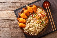 Delicious fast food crab claws in breading with egg noodles and. Fresh vegetable salad close-up on a plate on a table. horizontal top view from above stock image