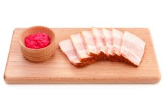 Delicious fat pork jowl bacon with horseradish sauce on wooden plate. Isolated on white royalty free stock images