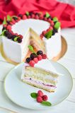 Delicious festive cake with fresh raspberries, blackberries and. Rosemary on a wooden white table Stock Photography